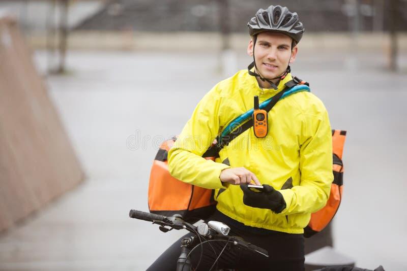 Männlicher Radfahrer mit Kurier-Bag Using Mobile-Telefon lizenzfreie stockfotografie