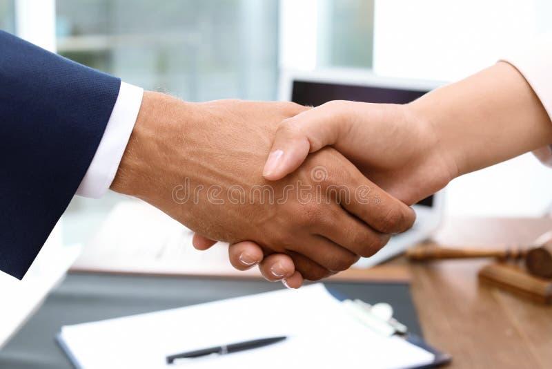 Männlicher Rechtsanwalt, der Hände mit Frau über Tabelle rüttelt stockbilder