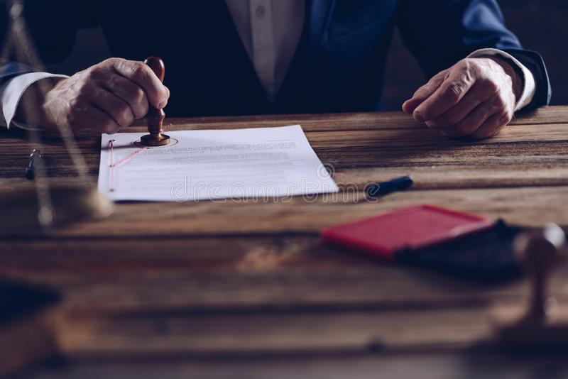 Männlicher Rechtsanwalt oder Notar, die Dokument in seinem im Büro stempeln stockbilder