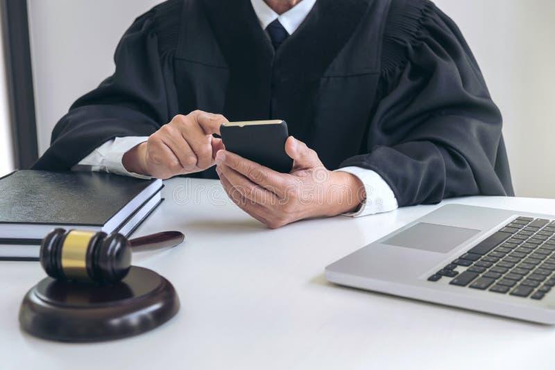 Männlicher Rechtsanwalt oder Richter, die mit intelligentem Telefon und Skalen von gerade arbeiten lizenzfreies stockfoto