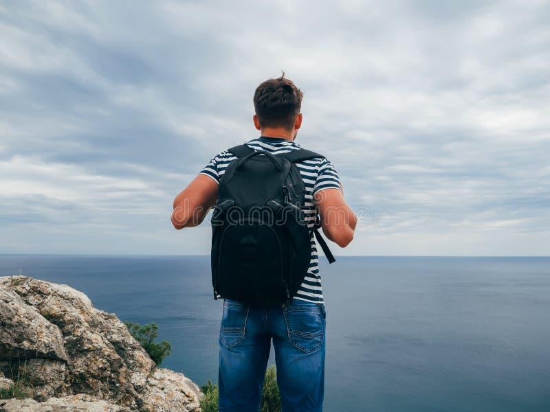 Männlicher Reisender mit einem Rucksack auf ihrem auf Seehintergrund-Sommernatur zurück stehen stockfoto