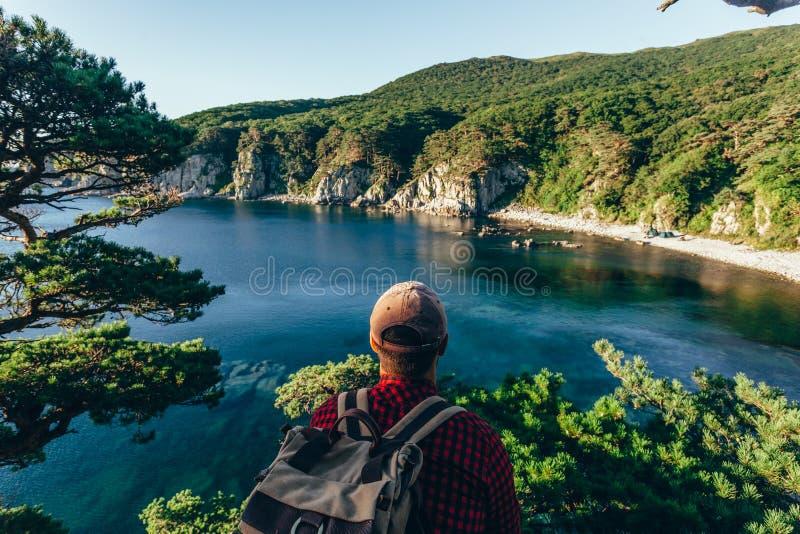 Männlicher Reisender von der Rückseite auf der Seeküste lizenzfreies stockbild