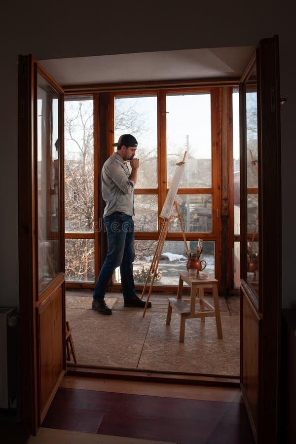Männlicher Schöpfer, der an einem Bild im Kunststudio arbeitet lizenzfreie stockfotos