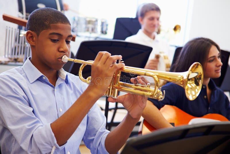 Männlicher Schüler, der Trompete in Highschool Orchester spielt lizenzfreies stockfoto