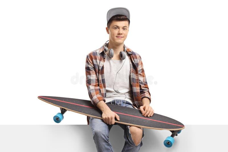 Männlicher Schlittschuhläufer mit einem longboard, das auf einer Platte sitzt stockfotografie