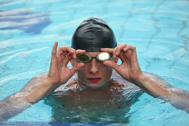 Männlicher Schwimmer, der Schutzbrillen justiert stockbilder