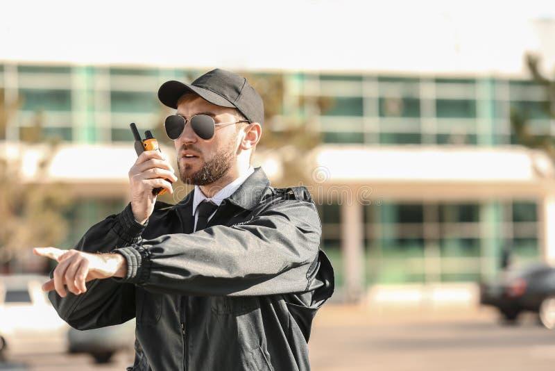 Männlicher Sicherheitsbeamte mit Übermittler des portablen Radios draußen lizenzfreie stockbilder