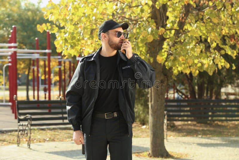 Männlicher Sicherheitsbeamte mit Übermittler des portablen Radios draußen lizenzfreies stockfoto