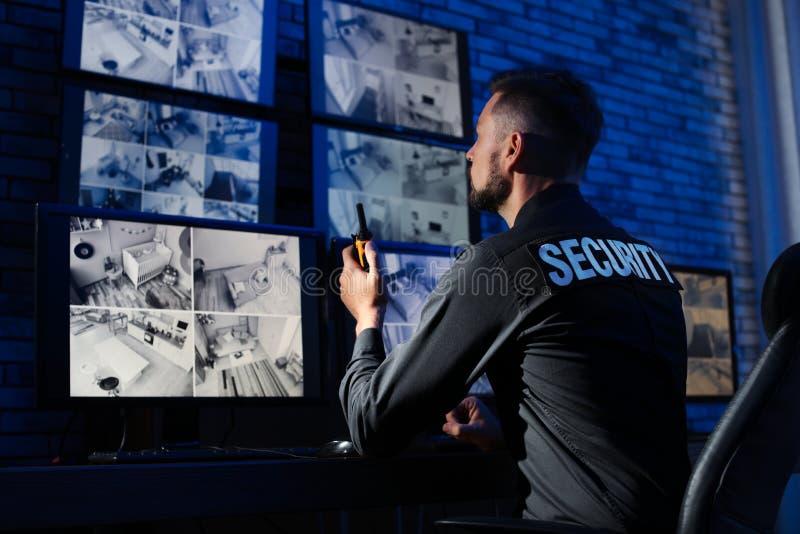 Männlicher Sicherheitsbeamte mit dem tragbaren Übermittler, der moderne Überwachungskameras überwacht stockfotos