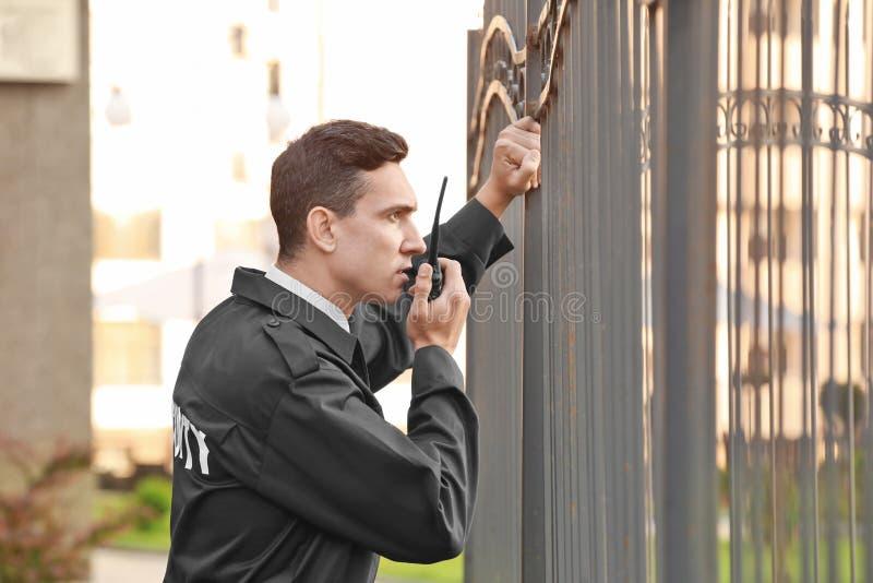 Männlicher Sicherheitsbeamte mit portablem Radio, stockbilder