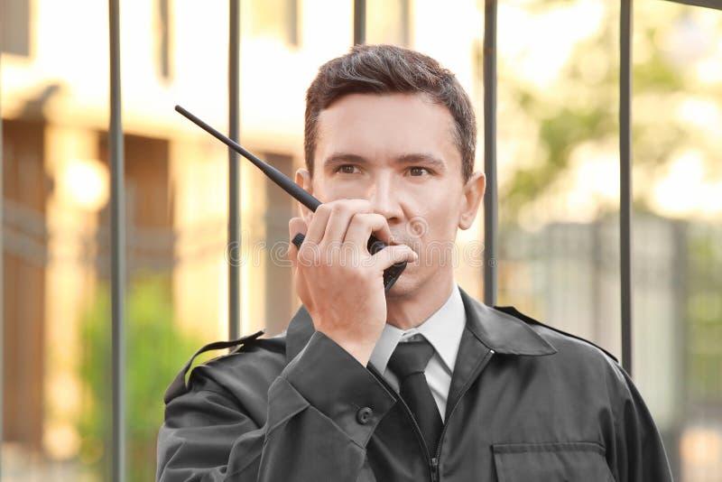 Männlicher Sicherheitsbeamte mit portablem Radio, stockfotografie