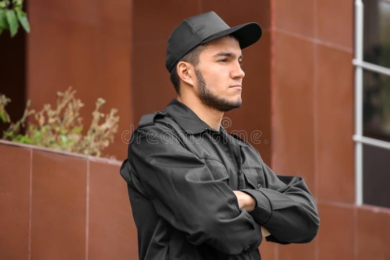 Männlicher Sicherheitsbeamte nahe Gebäude lizenzfreie stockfotos