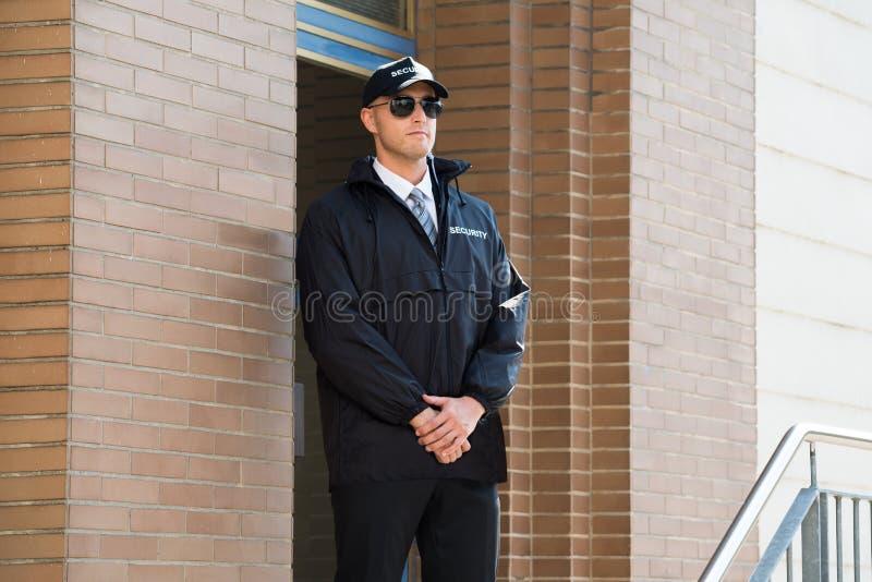 Männlicher Sicherheitsbeamte-Standing At The-Eingang lizenzfreies stockfoto