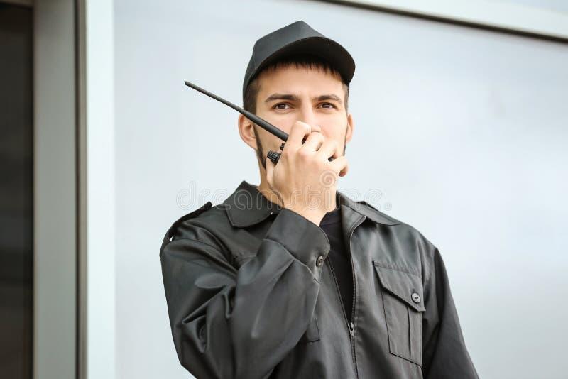 Männlicher Sicherheitsbeamte unter Verwendung des Übermittlers des portablen Radios stockfotos