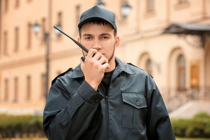 Männlicher Sicherheitsbeamte unter Verwendung des Übermittlers des portablen Radios lizenzfreie stockfotografie