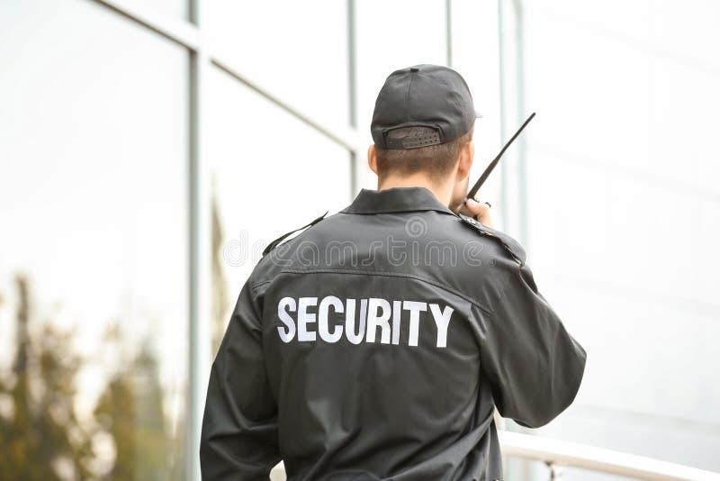 Männlicher Sicherheitsbeamte unter Verwendung des Übermittlers des portablen Radios stockfotografie