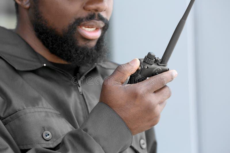 Männlicher Sicherheitsbeamte unter Verwendung des Übermittlers des portablen Radios lizenzfreies stockfoto