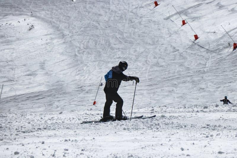 Männlicher Skifahrer, der nachdem dem Ski fahren stillsteht Eine Jungenstellung mitten in abschüssigem und Ansicht zum Tal auf Ch lizenzfreies stockfoto