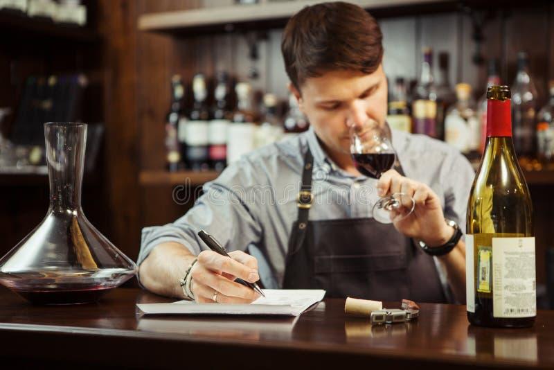 Männlicher Sommelier, der Rotwein schmeckt und Anmerkungen am Barzähler macht lizenzfreie stockbilder