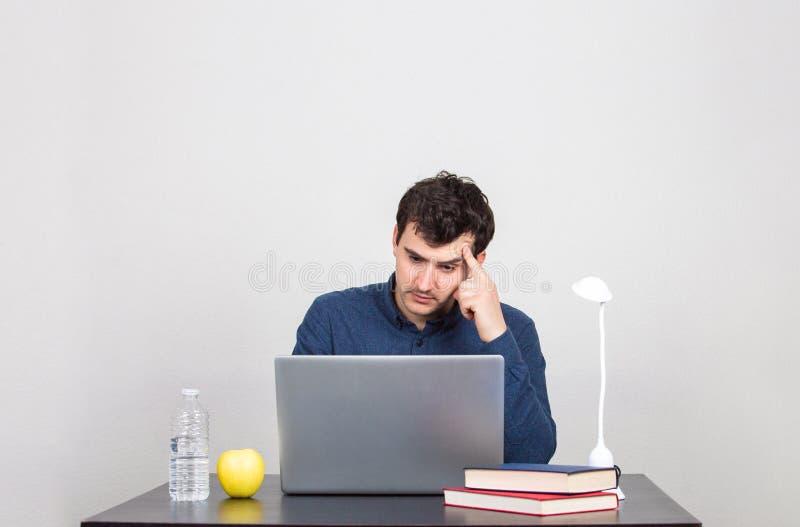 M?nnlicher Student, der denkt ein lapto intensiv, betrachtend stockfoto