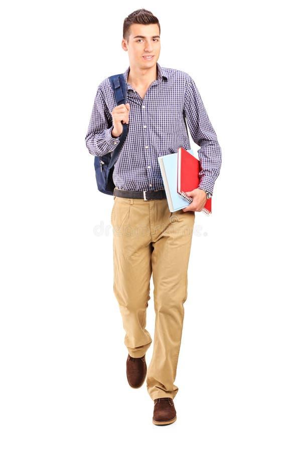 Männlicher Student, der mit Rucksack geht stockfoto