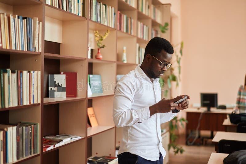 Männlicher Student des Afroamerikaners, der für Prüfungen in der Bibliothek sich vorbereitet lizenzfreies stockfoto
