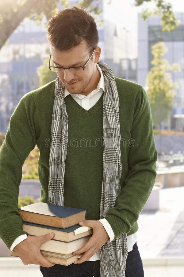 Männlicher Student mit Büchern draußen stockfotografie