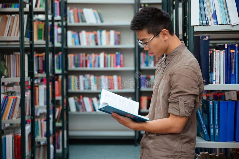 Männlicher Studenten-Reading Book In-Bibliothek stockfotografie