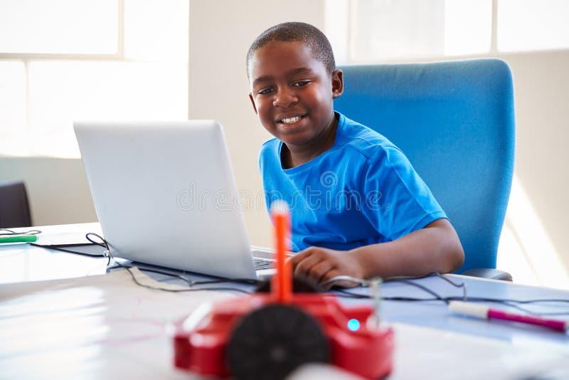 Männlicher Studenten-In After School-Computer, der die Klasse lernt, Roboter-Fahrzeug zu programmieren kodiert stockfotografie