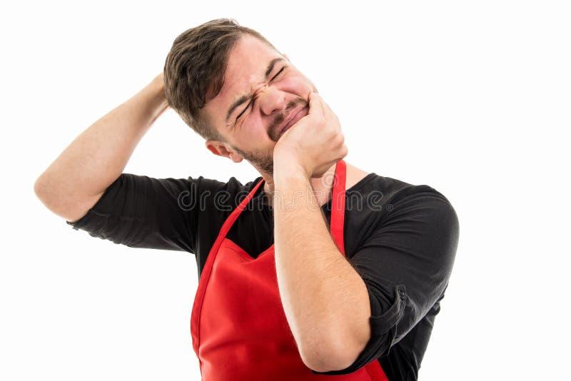 Männlicher Supermarktarbeitgeber halten Haupt wie das Ausdehnen seines Halses stockfotografie