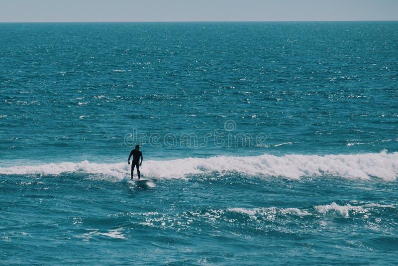 Männlicher Surfer im Ozean, Sommerhintergrundkonzept stockbild