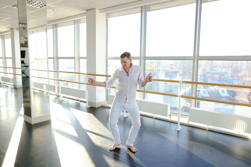 Männlicher Tänzer, der Schleifen im schwarzen Anzug am Studio macht stockbild