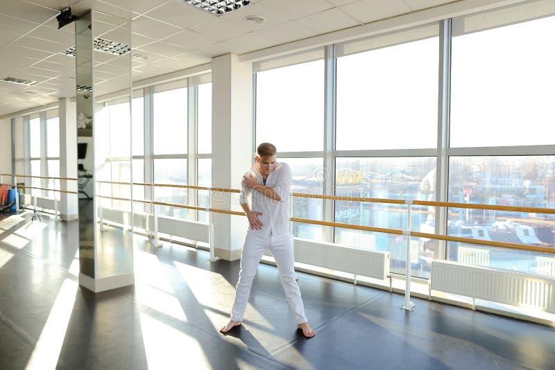 Männlicher Tänzer, der Schleifen im schwarzen Anzug am Studio macht lizenzfreies stockfoto