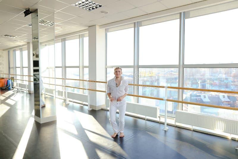 Männlicher Tänzer, der Schleifen im schwarzen Anzug am Studio macht lizenzfreie stockfotos