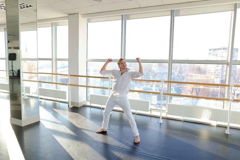 Männlicher Tänzer, der Schleifen im schwarzen Anzug am Studio macht lizenzfreies stockbild