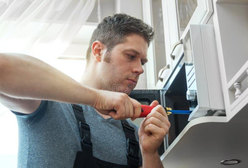 Männlicher Techniker, der Mikrowellenherd repariert lizenzfreie stockbilder
