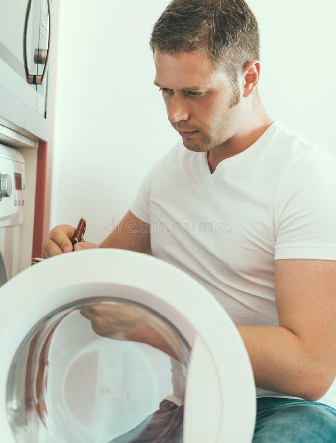 Männlicher Techniker, der Waschmaschine repariert lizenzfreie stockfotos