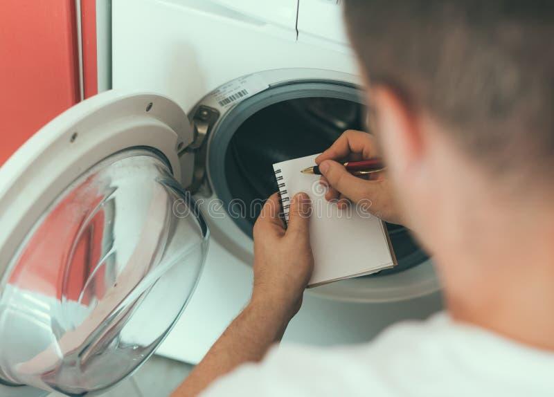 Männlicher Techniker, der Waschmaschine repariert lizenzfreie stockbilder