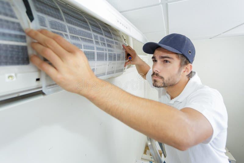 Männlicher Techniker des Porträtmittelerwachsenen, der Klimaanlage repariert stockfotografie