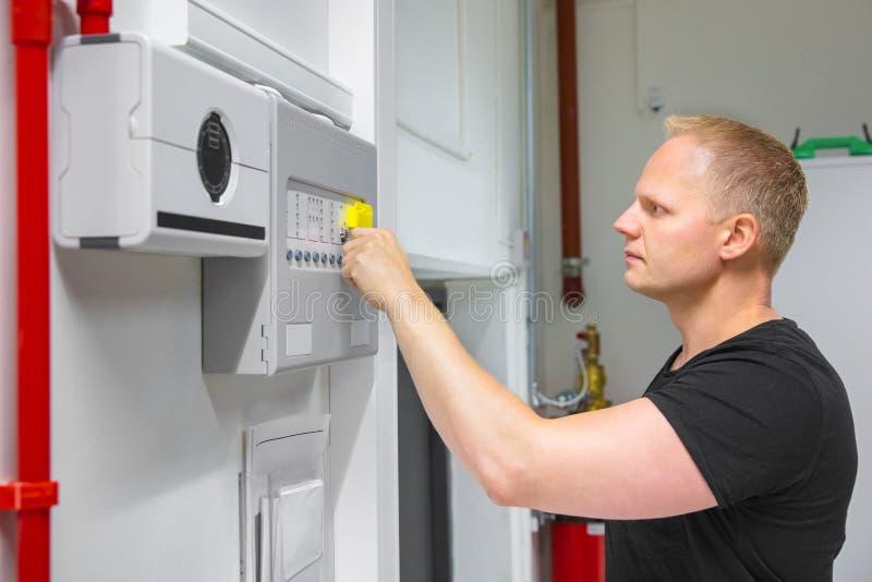 Männlicher Techniker Opening Fire Panel im Rechenzentrum stockbilder