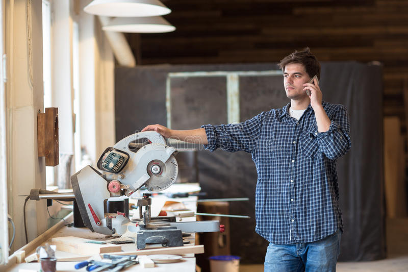 Männlicher Tischler im Zimmereishop am Telefon, Mann bei der Arbeit, lif lizenzfreie stockfotos