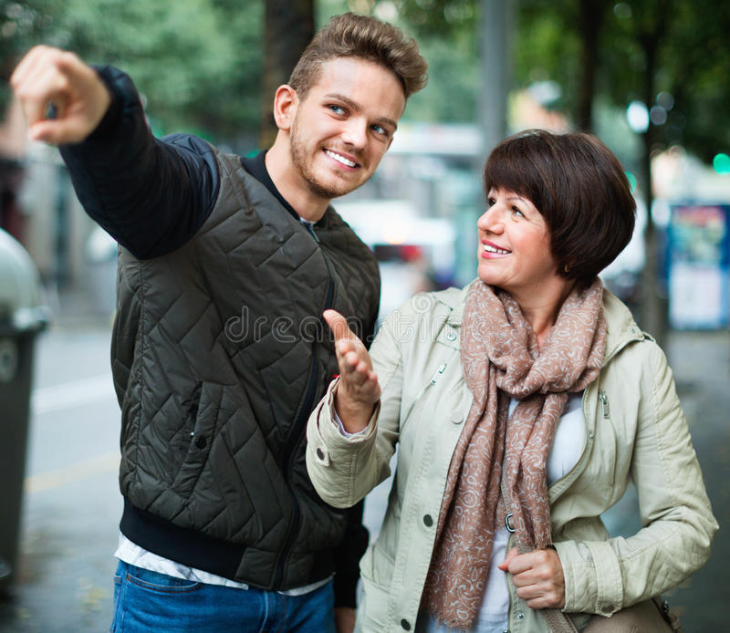 Männlicher Tourist bittet um Richtungen von der Frau lizenzfreie stockbilder