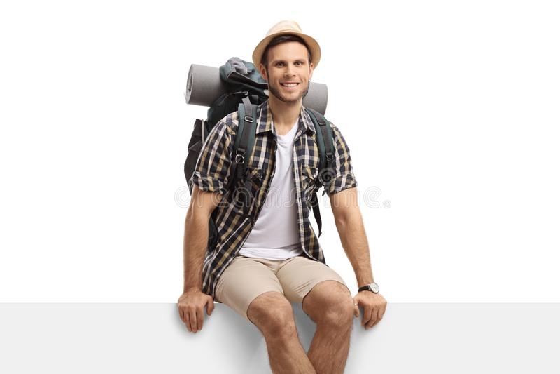 Männlicher Tourist, der auf einer Platte sitzt und die Kamera betrachtet stockfotografie
