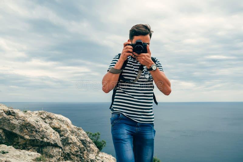Männlicher Tourist des Fotografen mit einer Berufsdigitalkamera und einer Linse lizenzfreies stockbild