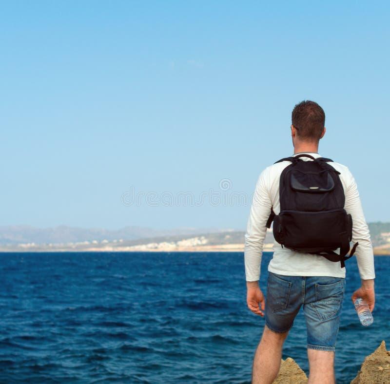 Männlicher Tourist nahe dem Meer lizenzfreie stockbilder