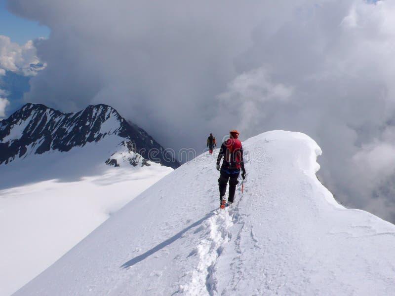 Männlicher und weiblicher Bergsteiger, der von einem hohen alpinen Gipfel entlang einer schmalen Schnee- und Eiskante absteigt stockbild