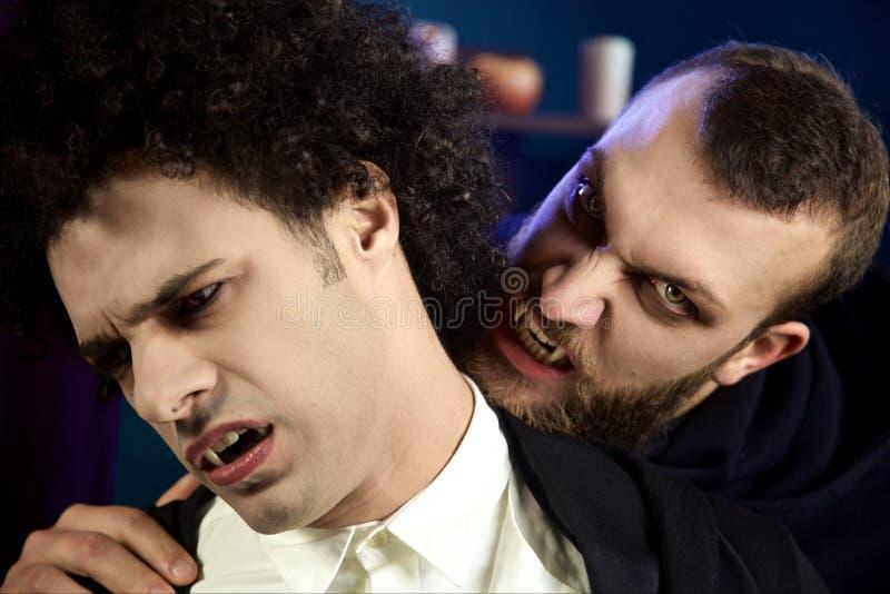 Männlicher Vampir, der anderen hoffnungslosen Vampir angreift stockbilder