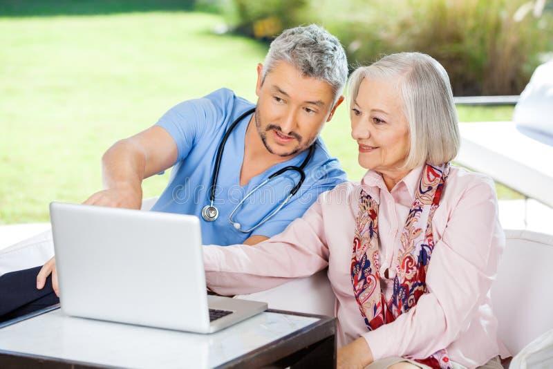Männlicher Wärter, der ältere Frau bei der Anwendung unterstützt lizenzfreies stockbild