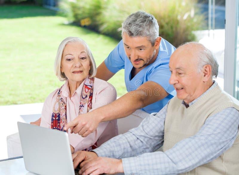 Männlicher Wärter, der ältere Paare bei der Anwendung unterstützt stockfotos