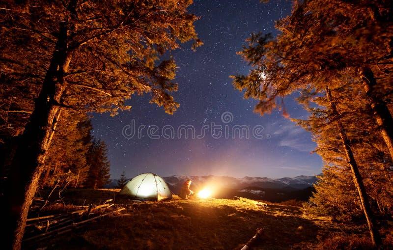 Männlicher Wanderer haben einen Rest in seinem Lager nahe dem Wald nachts unter schönem nächtlichem Himmel voll von Sternen und v lizenzfreie stockfotos